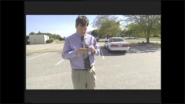 1990s: Person holds module attached to key chain. Man walks away from car then stops and goes back to car. Man takes baby out of car seat. Woman talks. Man talks.