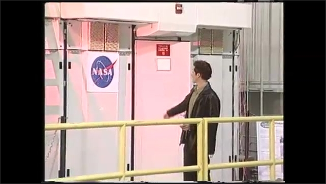 1990s: Man exits door in lab while talking then points to NASA emblem on wall. Man talks.