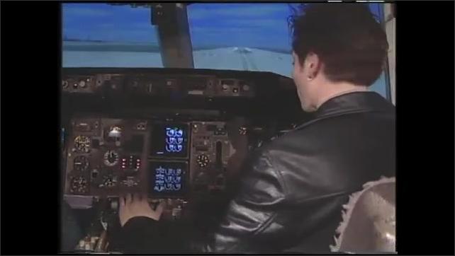 1990s: Man sits in cockpit of flight simulator. Images on screen in flight simulator of plane in flight. Man shows other man how to fly simulator. Man flies simulator.