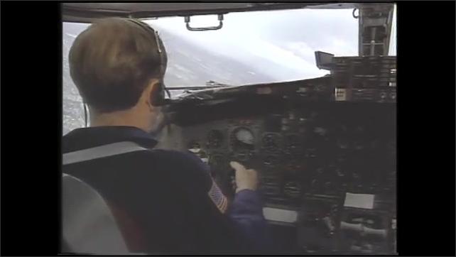 1990s: Gauge in cockpit of airplane. Man flies plane. Controls in cockpit.