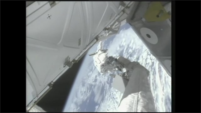 1990s: Astronaut works on experiments during spacewalk. Astronauts on spacewalk work with experiment case.