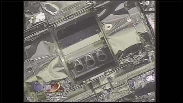 1990s: Man and woman take in laboratory. Exhaust system turns and spins on space station. Man speaks in lab.