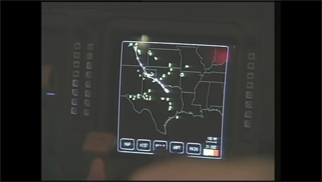 1990s: Man speaks in aircraft hangar. Man pilots airplane. Hands operate digital controls in cockpit. Digital clouds pass over map on screen. Men bounce in turbulent plane.