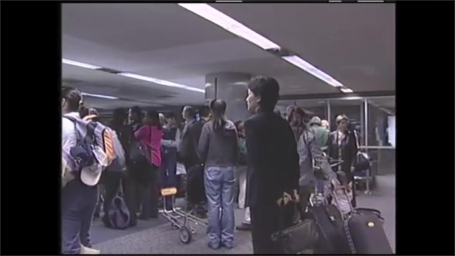 1990s: Plane crashes. People walk in airport terminal. People in airport. Man talks.
