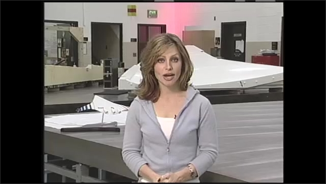 1990s: Model of plane in lab. Researchers work on model plane. Woman speaks. Plane takes off.