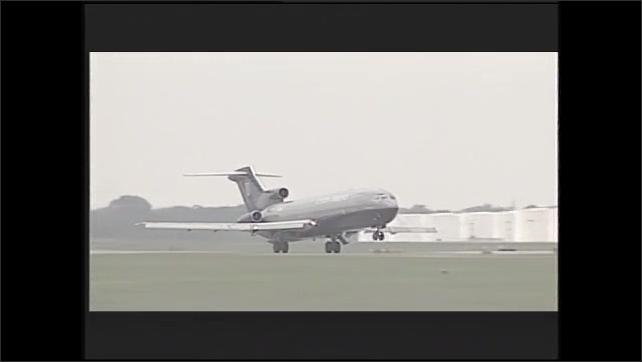 1990s: Plane in flight. Man speaks. Woman speaks and gestures. Plane takes off.
