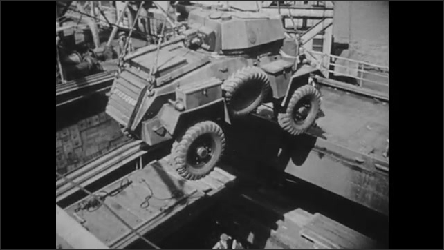 1940s: UNITED KINGDOM: EUROPE: ships loading weapons in port. Man in port directs with hand. Man packs sacks on ship.