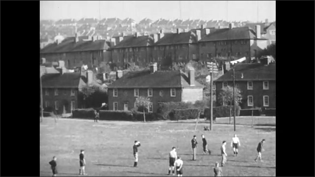 1940s: UNITED KINGDOM: people walk through town in Britain. Children walk along terraced street. Man smiles. Church in town. Mining town. Men play football on green. People at market