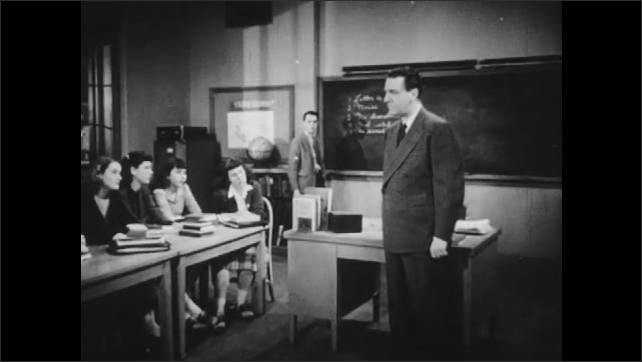 1940s: Young man writes on chalkboard.  Teacher stands.  People speak.