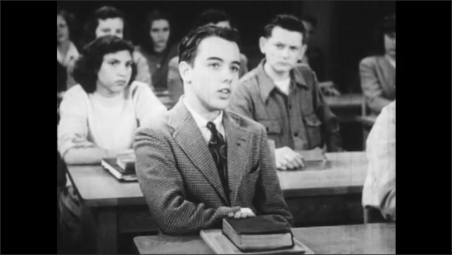 1940s: Classroom.  Students and teacher talk.