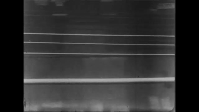 1930s: View of buildings from balcony, person exits door. Tracking shot of city street from train.