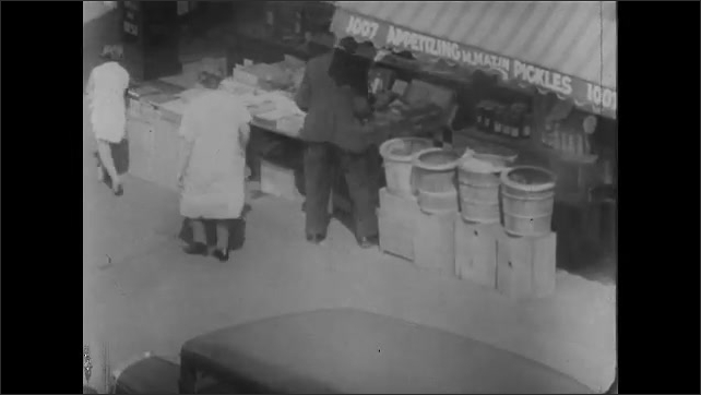 1930s: High angle view, city street corner. View of storefront, people on sidewalk. Sign above store, tilt down. Woman sitting outside store.