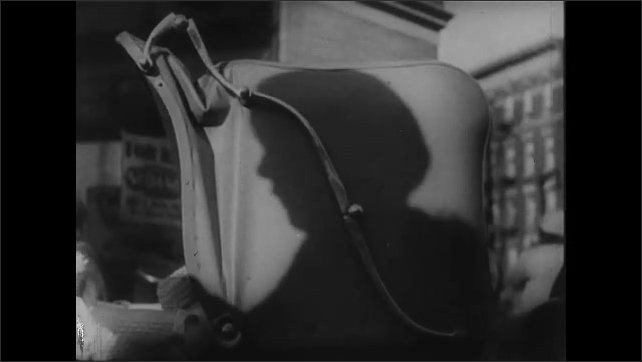 1930s: Woman rocking baby carriage. Baby being rocked. Shadow of woman on carriage. Baby being rocked in carriage. Woman climbs steps with child, tilt up to side of building.