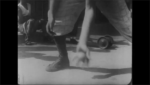 1930s: Water flowing in gutter. Girl crouched on sidewalk. Boy next to fire hydrant. Close up, boy's hands throwing ball. Shadow of boy playing. Feet on sidewalk.