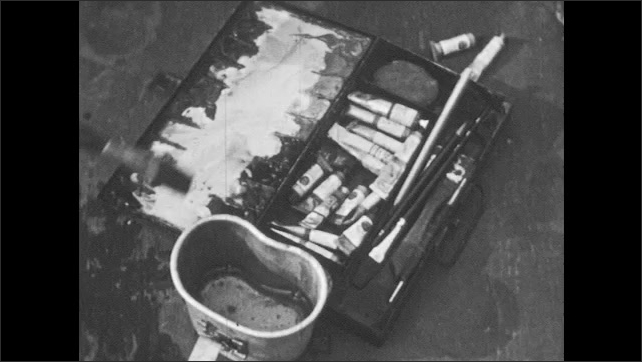 1950s: Box of watercolor paints, hand picks up brush, dips brush in water, wipes off brush, sets brush down, picks up tube of paint, unscrews cap.