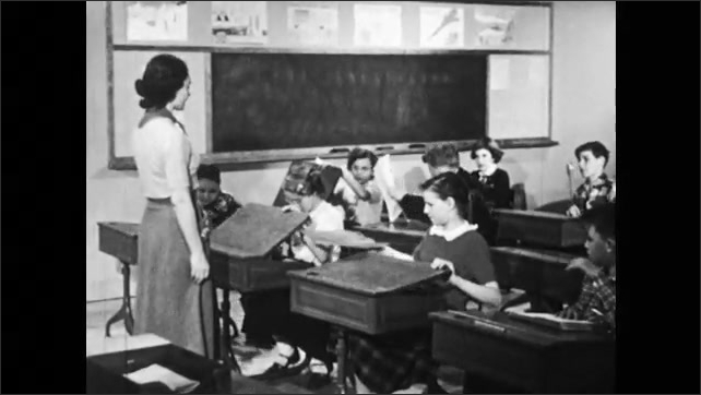 1950s: Teacher talks to students in classroom who have their hands raised. Students take papers from desk and start working together.
