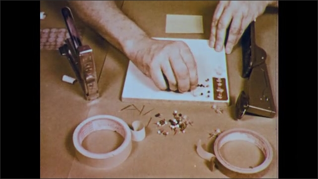 1950s: hands stick various kinds of pins on display board, tear off piece of masking tape and stick it to paper staplers nearby