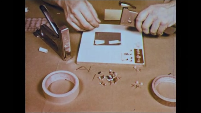 1950s: hands tear double-sided tape, finger points to tape, places it on paper, hands use automatic stapler and desk stapler to staple paper to display board, hands place paper on tape, show board