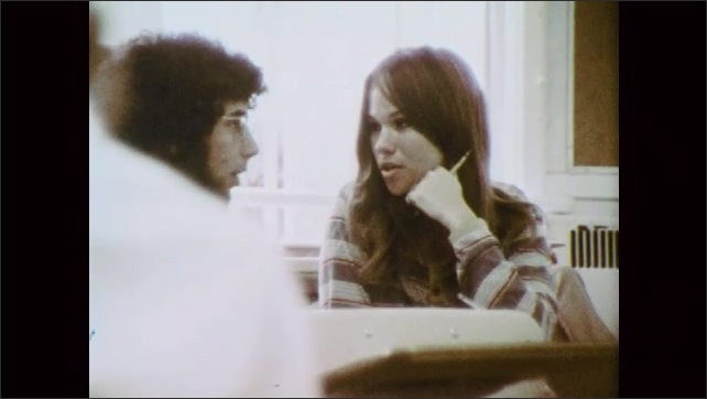 1970s: UNITED STATES: girl sits in classroom. Girl listens to lecture. Girl talks to boy in class.
