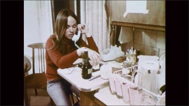 1970s: UNITED STATES: girl sits in kitchen. Lady talks on telephone. Girl puts down telephone