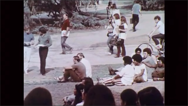 1970s: UNITED STATES: students walk through university campus. Students sit on grass. Girl drinks coffee.