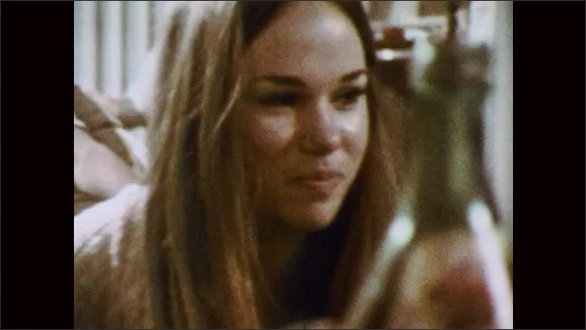 1970s: UNITED STATES: stoned young people at home. Girl smiles. Girl takes sip of drink. Girl smokes cigarette