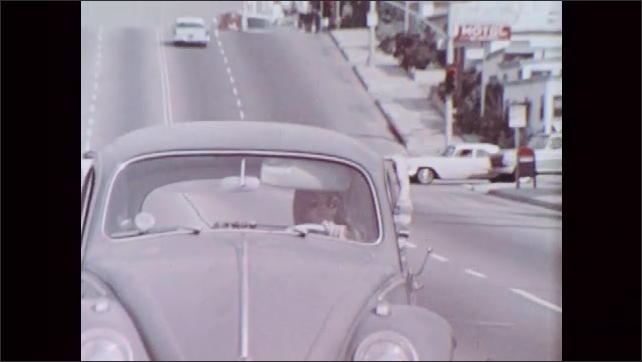 1970s: UNITED STATES: side profile of girl in car. Girl drives car. Front view of car driving along road. Girl with hand out of car window