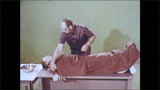 1970s: Man with burns lays on table. Doctor covers burns with gauze. Man on table with legs elevated. Doctor covers man with blanket and helps him drink water. Severe burn on palm, man inspects burn.