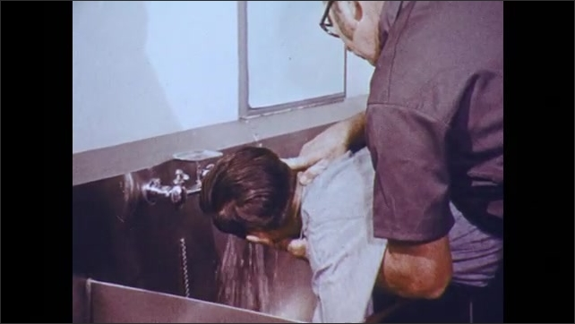 1970s: Man with wet shirt rubs eyes in pain. A second man guides the injured man to utility sink, holds face under running water.