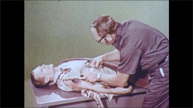 1970s: Man with tattered clothes and third degree burns lays on table. Doctor uses medical scissors to cut clothes away from burns.
