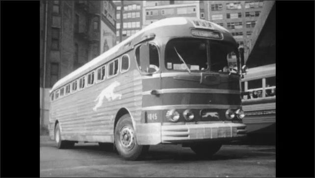 1940s: Man and boy walk away from ticket window, look at tickets. Bus pulls into station.
