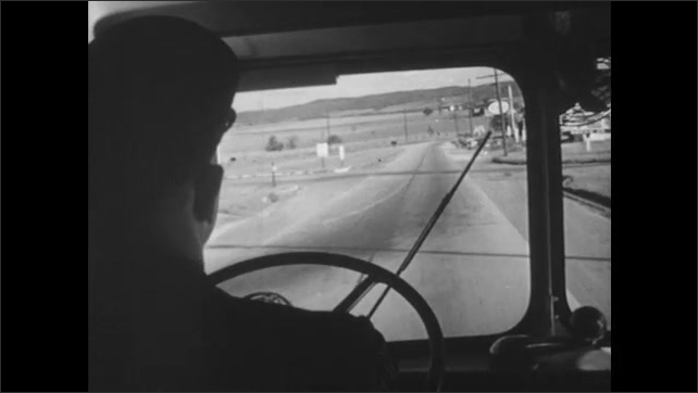 1940s: Bus drives down highway, cars and trucks go past in the other direction. Bus driver holds steering wheel, drives bus. Bus stops at traffic light.