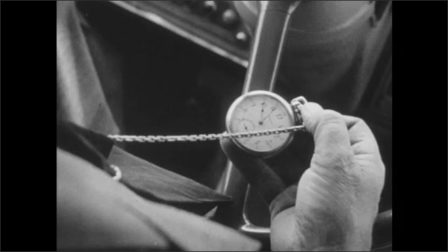 1940s: Bus sits at red light, cars goes across intersection. Bus driver checks time on pocket watch. Bus driver looks up, shifts gears.