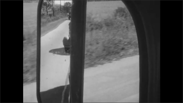 1940s: Bus drives down highway. Car passes another car, comes into oncoming traffic in front of bus. Bus driver looks at side view mirror, two cars pass bus.