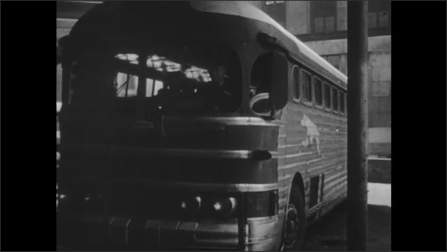 1940s: Bus pulls into bus station. Attendant helps man and boy unload luggage from compartments on side of bus. Man and boy wave at bus driver, driver waves. Driver steps into bus. Bus door closes.