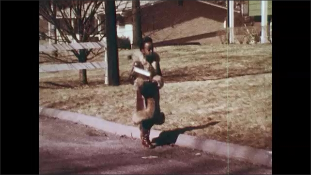 1970s: Young girl in fur-trimmed coat holding books walks across yard and down the street. Girl in pink dress walks down driveway.