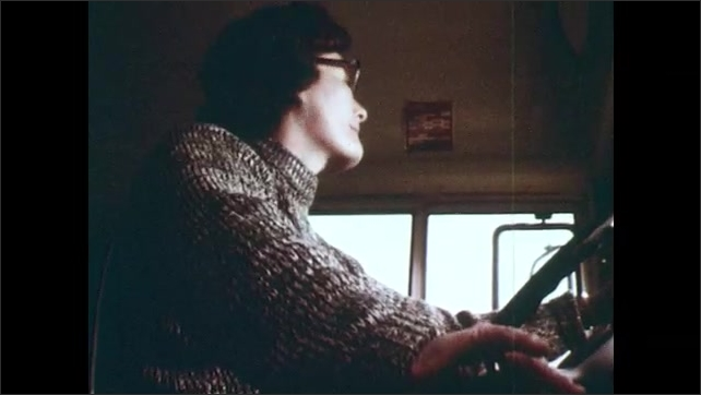 1970s: Bus driver pulls lever to close door. Reflection of bus driver and smiling girl in fur-trimmed coat in rearview mirror. Bus driver drives. Bus driver