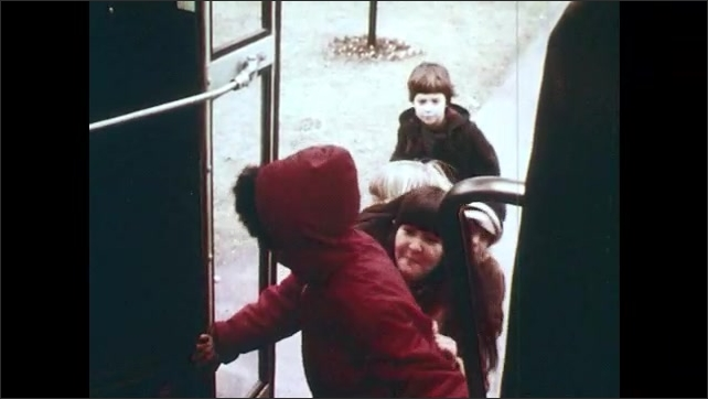 1970s: Side view mirrors on bus in motion. Family with dog walk down street toward waiting children. Bus arrives to pick up children. Children board bus pushing and shoving at first, and then calmly.