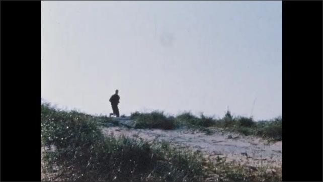 1960s: Man runs on beach, runs past space shuttle launch pad. Scaffolding surrounds space shuttle.
