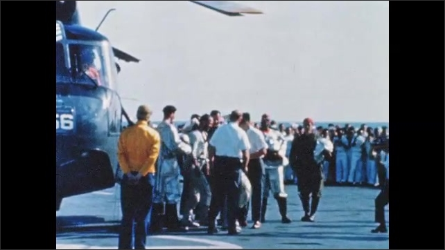 1960s: Helicopter lands on aircraft carrier. Astronauts exit helicopter, walk across deck of carrier.