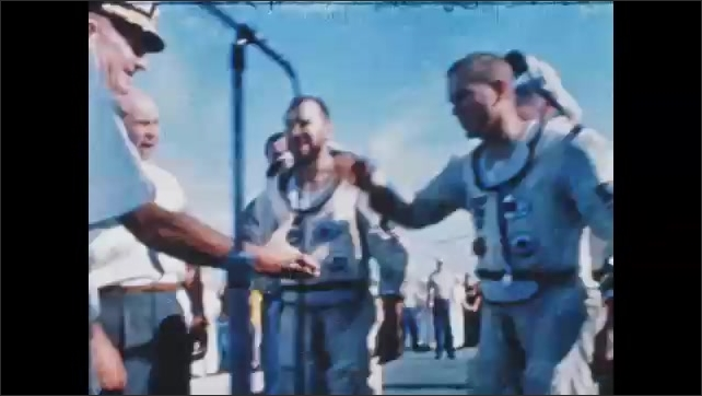 1960s: Astronauts walk across deck of aircraft carrier, smile, talk, and shake hands with people.