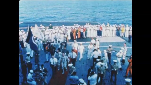 1960s: Astronauts walk across deck of aircraft carrier, smile, talk, and shake hands with people. Man slides down zip line, is pulled across water, runs with parachute on back.