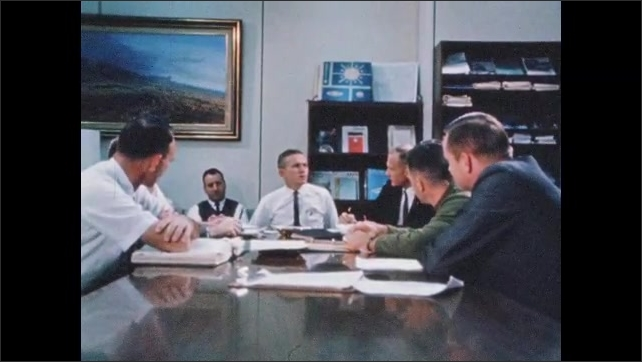 1960s: Men sit around table in conference room, talk. Astronauts sit around table, talk.