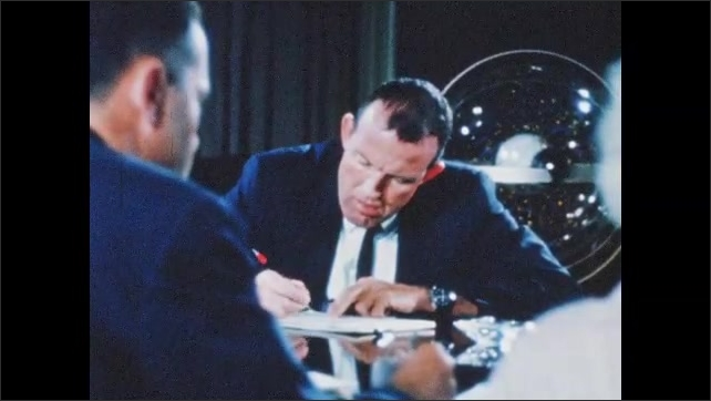 1960s: Men seated around table. Astronauts in suits with men. Men putting equipment on astronauts. Man at table. Man talking in front of chalkboard. Views of man on airplane.