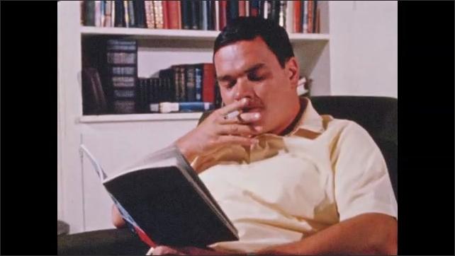1960s: View over shoulder, man looks at pamphlet. Man reading, drinks beer. Hand sets down beer bottle. Man reading, smoking. Man reading pamphlet.