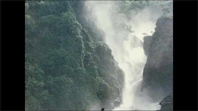 1960s: Murchison Falls, rapid water stream with mist, foam on rapid water between rocks, water splashes. Woman stands on boat and watches the landscape. Cloudy sky reflects on the surface of a river.