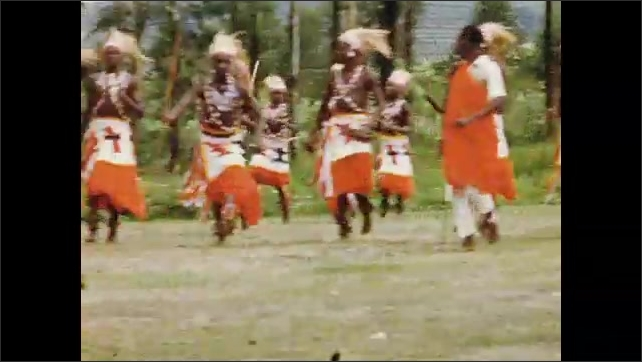1960s: African man dances solo in a ceremony, a man throws a stick to the ground. African tribesmen walk behind each other and perform. African tribesmen dance in group, wear costumes and hold sticks.