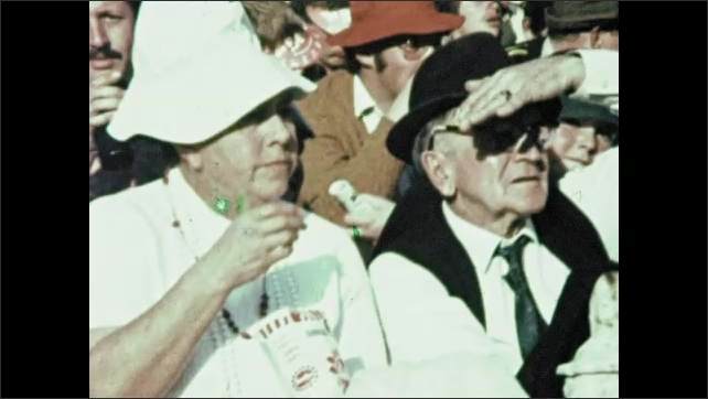 1970s: AFRICA: South Africans in crowd. Man shields eyes from sun. Lady eats packet of food in chair