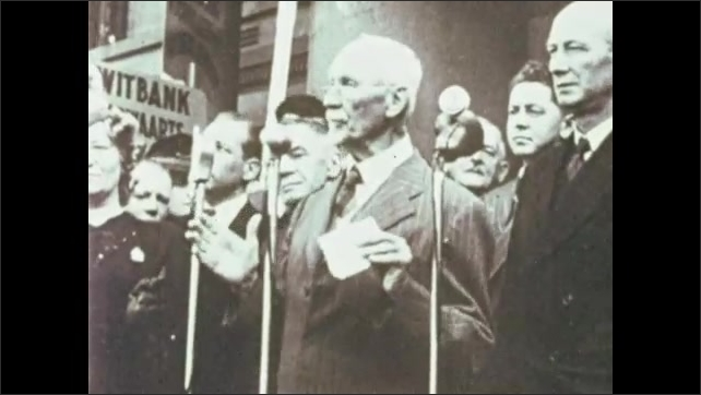 1970s: AFRICA: men pull on chains. Man gives talk by microphone. British wars and racial dominance. Jan Smuts addresses crowd.