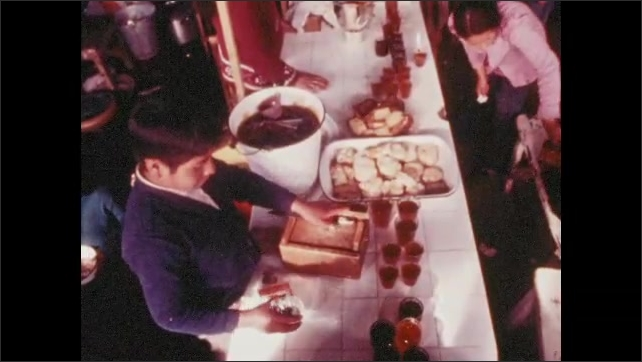 1970s: People set out food and drinks on table.